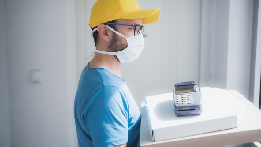 Deliveryman with protective medical mask holding pizza box and POS wireless terminal for card paying - days of viruses and pandemic, food delivery to your home and safety hygiene measures. Royalty-Free Stock Footage #1049469016