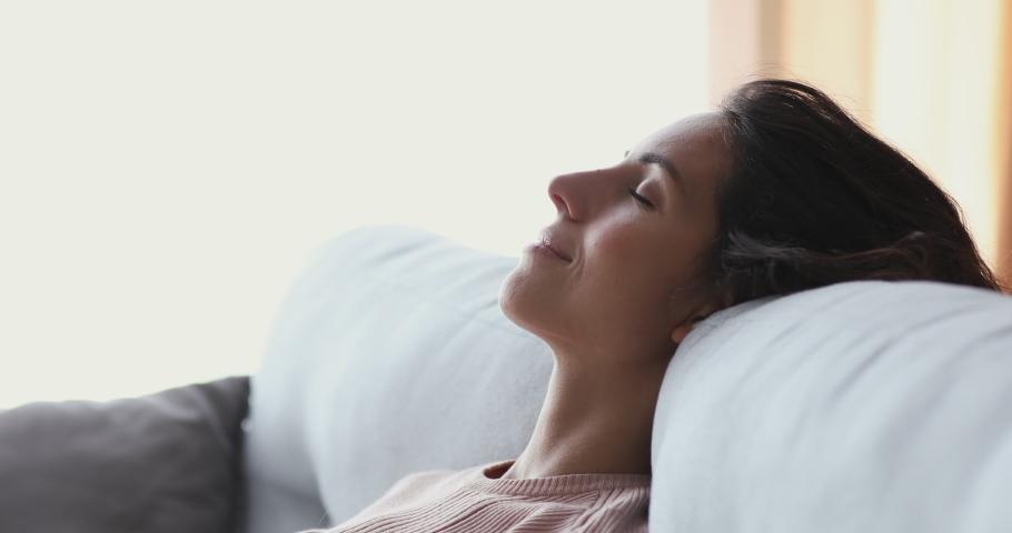 Healthy serene young woman leaning on cozy sofa taking deep breath of fresh clean air. Calm lady relaxing on comfortable couch, napping, enjoying no stress concept at home, close up side face view. | Shutterstock HD Video #1049471794