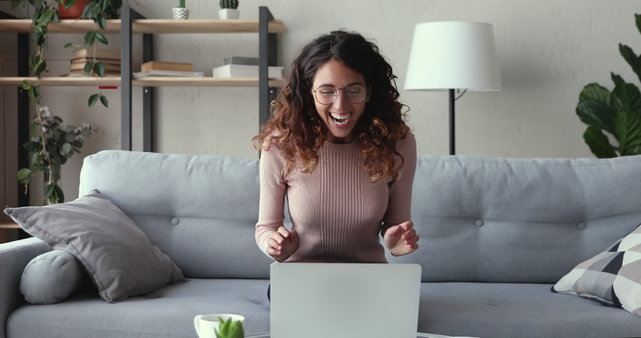 Excited young woman winner looks at laptop celebrates online success sits on sofa at home. Euphoric lady gets new distance job opportunity, reads good news in email, rejoices victory, feels motivated.
