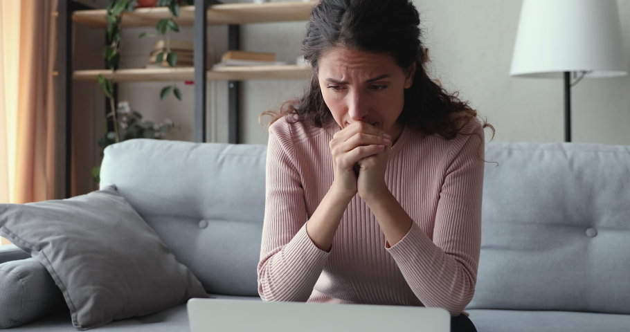Worried young adult woman looking at laptop feeling frustrated desperate reading bad negative online news sitting at home. Stressed upset female user using computer anxious about financial problems.