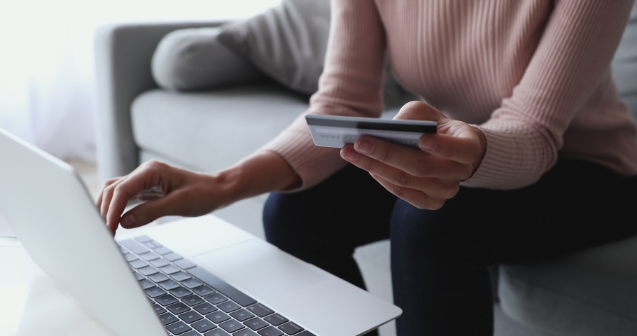 Woman customer using computer e-banking service making secure online payment holding credit card in hand. Female buyer paying on website via e commerce service sitting on sofa at home. Close up view Royalty-Free Stock Footage #1049471812
