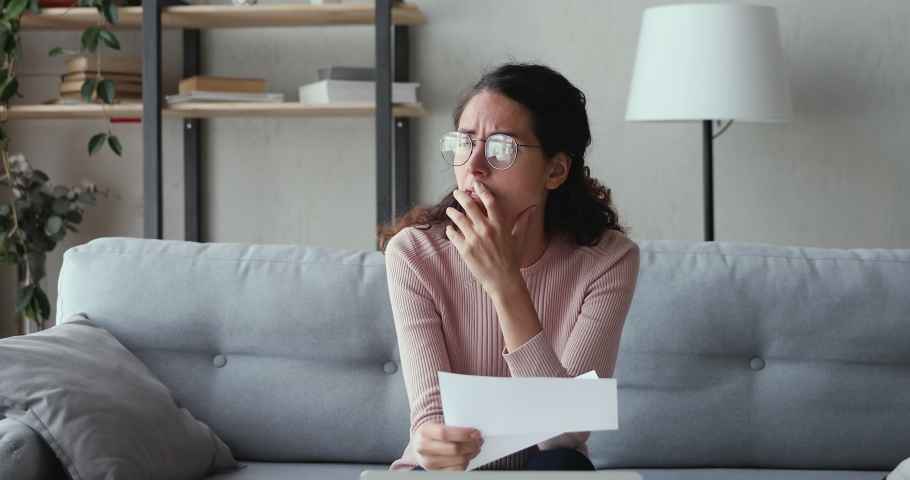 Stressed worried young woman reading bad news in paper mail letter at home. Desperate lady frustrated about bankruptcy, financial problem, receiving bank debt penalty, high bills, lost job concept. Royalty-Free Stock Footage #1049471824