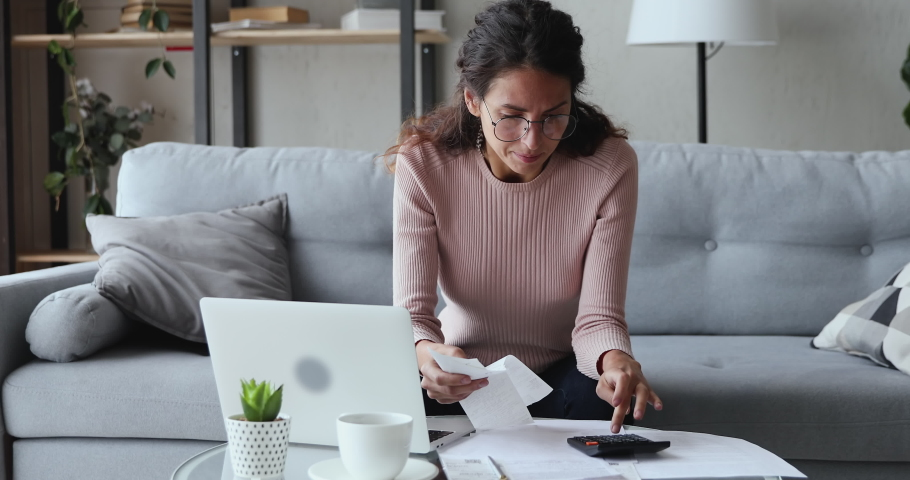 Stressed worried young woman feels panic about financial problem checking household payments. Frustrated female renter calculating bills, bank mortgage debt looking desperate about bankruptcy at home. | Shutterstock HD Video #1049471830