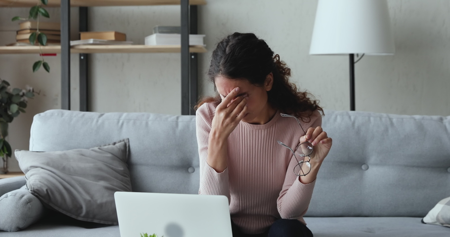 Exhausted young woman taking off glasses massaging dry irritable eyes. Tired overworked lady feeling eye strain after using computer working from home. Headache, visual fatigue and eyestrain concept. | Shutterstock HD Video #1049471836