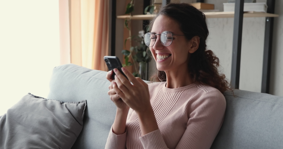 Excited young woman winner receiving good news in mobile sms message sitting on sofa at home. Happy lucky lady celebrating success, victory, win concept looking at smart phone winning bid or prize. Royalty-Free Stock Footage #1049471857