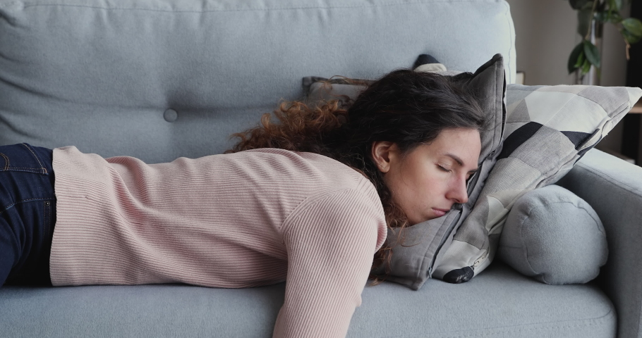 Exhausted or bored young sleepy woman falls down on sofa. Apathetic tired lazy lady sleeping on couch at home alone. Funny girl lying asleep feeling lack of motivation, fatigue or depression concept