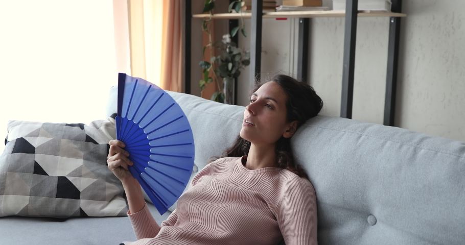 Tired unhappy young woman cooling herself waving fan suffering from summer heat discomfort at home. Sweaty overheated lady sitting on sofa feeling hot without air conditioner in apartment concept.