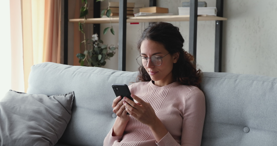 Relaxed young woman using smart phone surfing social media, checking news, playing mobile games or texting messages sitting on sofa. Millennial lady spending time at home with cell gadget technology.