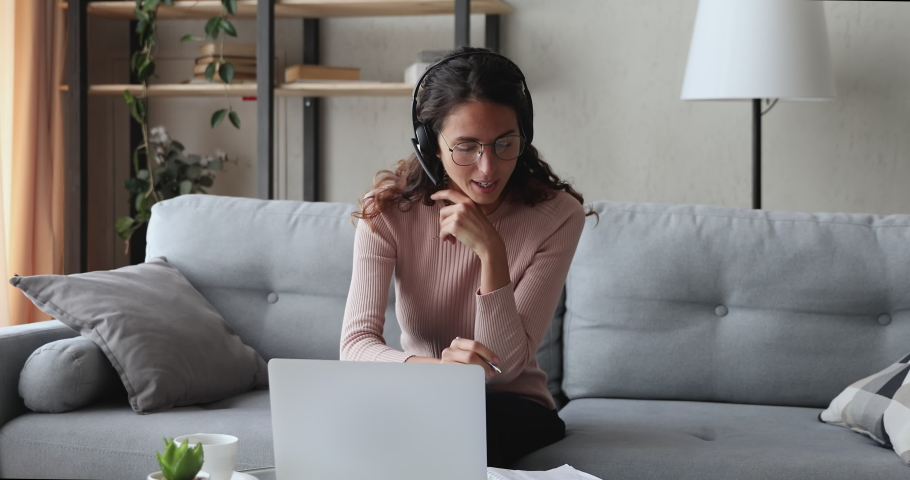 Young woman wears headset conference calling on laptop talks with online teacher studying, working from home. Lady student e learning using computer webcam chat makes notes. Distance education concept | Shutterstock HD Video #1049471893
