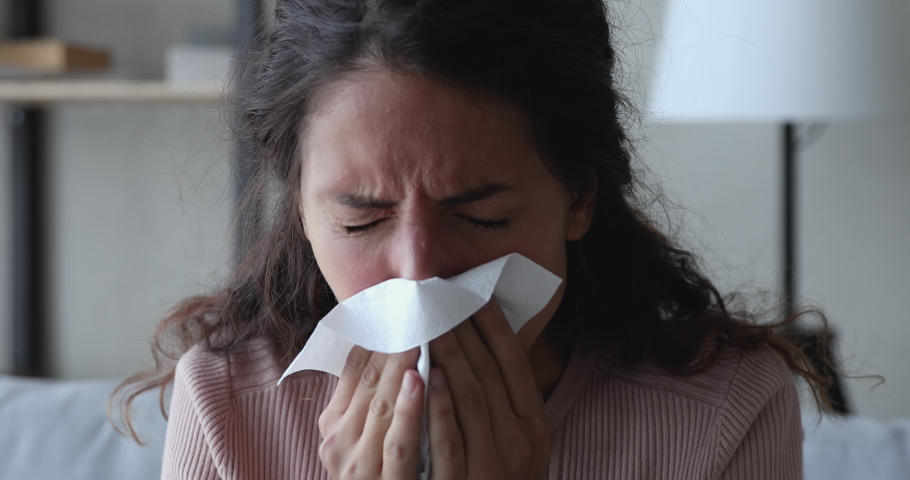Ill sick young woman sneezing in tissue, blowing runny nose. Millennial lady having flu coronavirus cold symptoms at home. Covid 19 virus infection, flu and seasonal allergy concept. Close up view Royalty-Free Stock Footage #1049471908