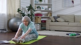 Tracking shot of senior woman watching video workout on laptop and doing stretching exercise on mat in the living room while exercising at home