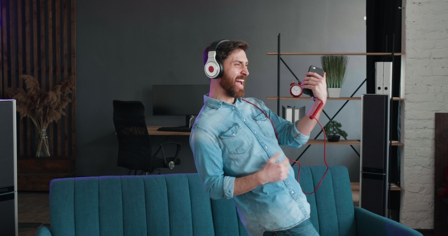 Slow motion of handsome Bearded guy have Fun jumping dancing on bed and listening to Music in Headphones. Man playing imaginary Guitar in Loft Living Room. Playfully Mood on Quarantine.