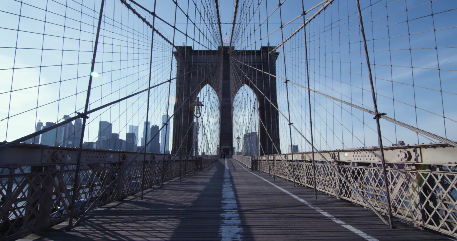 Brooklyn Bridge in New York City on a clear day with no foot traffic and Manhattan skyline in the background.