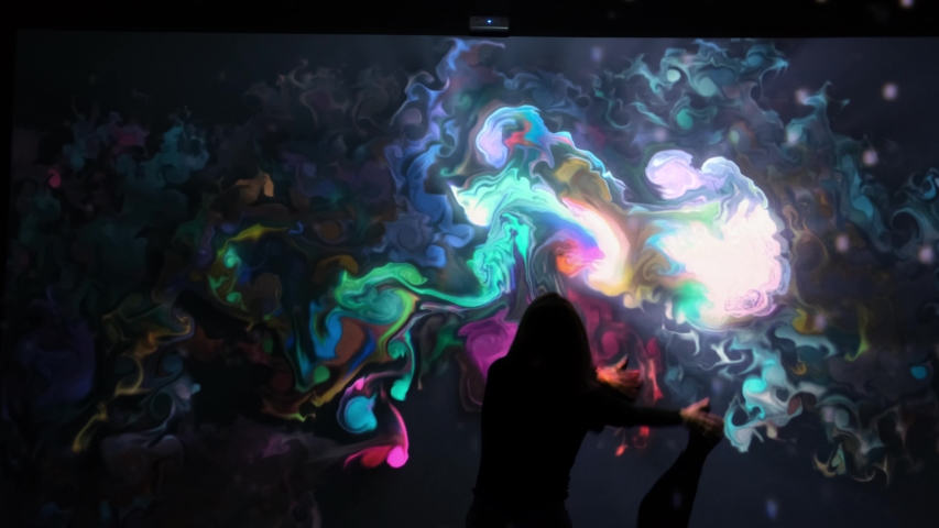 Girl plays with interactive video installation, New art form, generative graphics. Silhouette of girl draws multi-colored paints interactive installation. Woman does concept art with augmented reality | Shutterstock HD Video #1049499832