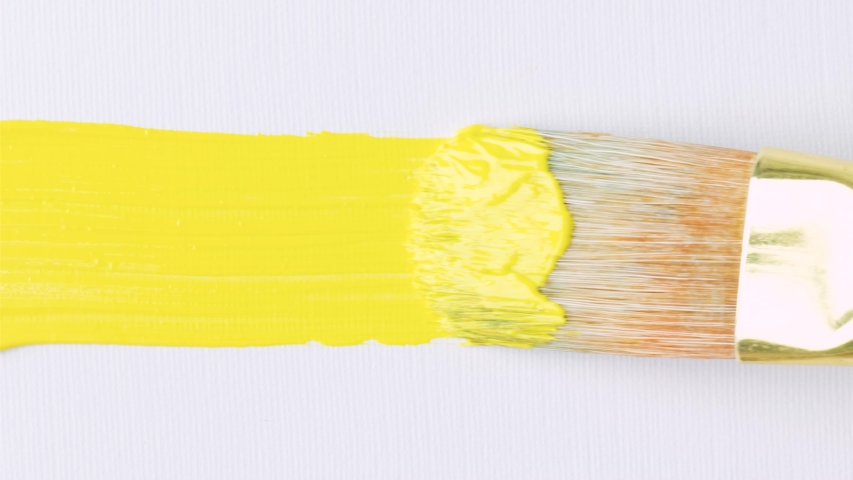 Close-up of artist holding paint brush and drawing oil painting. Painting yellow line on canvas. | Shutterstock HD Video #1049502079