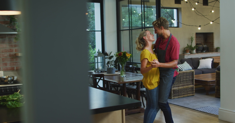 Caucasian couple enjoying their time at home, dancing in the kitchen, social distancing and self isolation in quarantine lockdown during coronavirus covid19 epidemic, in slow motion