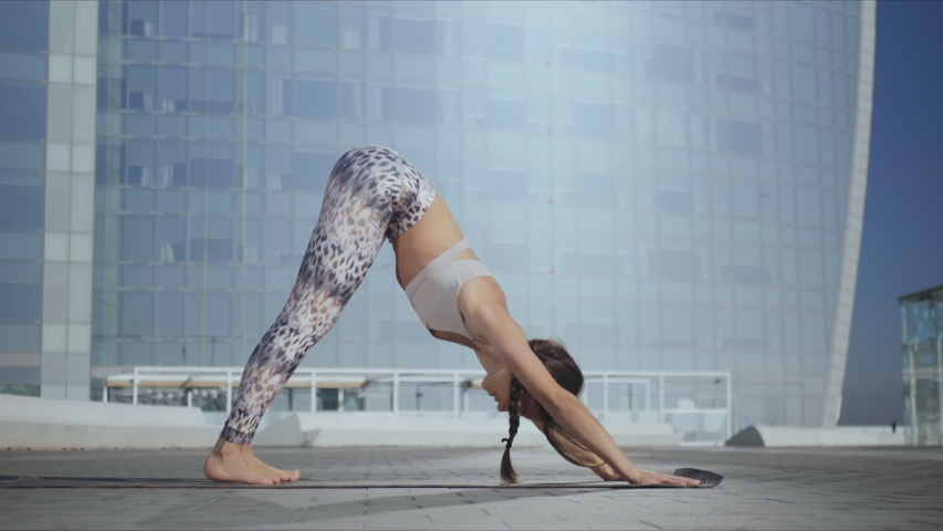 Yoga woman standing in upward facing dog pose outdoors. Fit girl doing flexibility exercises on street in slow motion. Sporty lady changing yoga pose into downward facing dog on city street Royalty-Free Stock Footage #1049507149