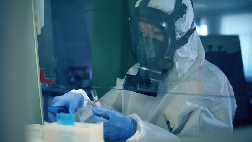 Coronavirus COVID-19 concept. A woman in a splash suit is working with test tubes in a laboratory Royalty-Free Stock Footage #1049509111