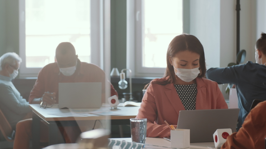 Mixed raced woman in protective face mask sitting at desk and typing on laptop while working in open space office with colleagues during coronavirus outbreak Royalty-Free Stock Footage #1049518969