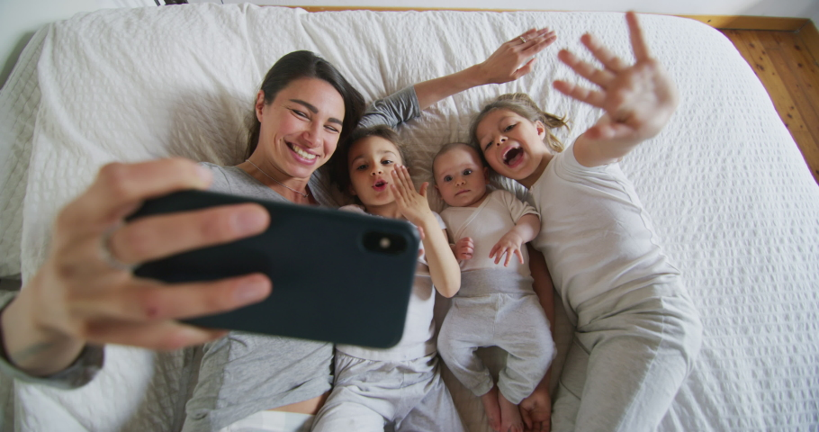 Authentic shot of happy mother with her kids are making a selfie or video call to father or relatives in a bed. Concept of technology, new generation,family, connection, parenthood, authenticity