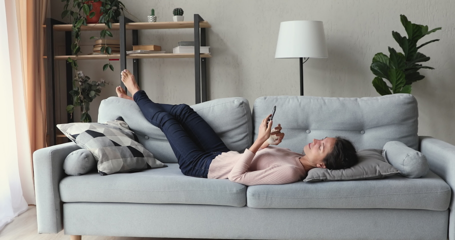 Relaxed young woman lying on sofa in living room using smart phone. Lazy happy millennial lady customer surfing social media, shopping in app, playing mobile game, texting sms looking at cell at home. Royalty-Free Stock Footage #1049522452
