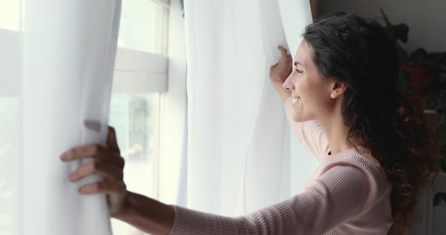Happy optimistic young woman opening curtain lace looking through window. Smiling confident lady enjoying watching beautiful cityscape view, feeling hope and dreaming of good future at home. | Shutterstock HD Video #1049522455