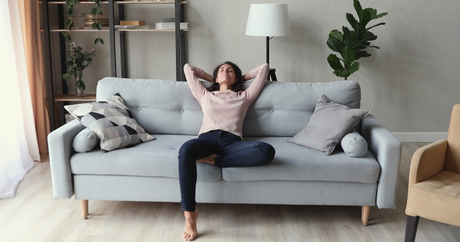 Calm young adult lady lounging on comfortable sofa in modern living room interior. Relaxed tired woman napping on couch hands behind head. Smiling girl feels no stress enjoying peaceful chill at home.   Shutterstock HD Video #1049522461