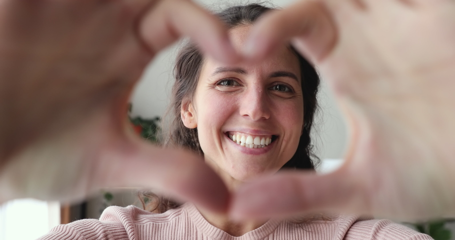 Smiling young woman volunteer showing hands sign heart shape looking at camera. Healthy heart health life insurance, love and charity, voluntary social work, organ donation concept, close up portrait.