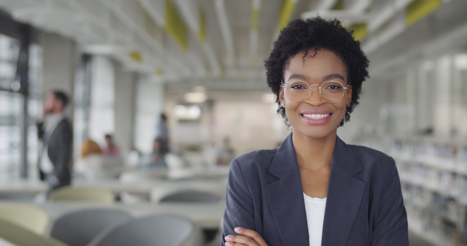 Successful millennial businesswoman in suit smiling and turning head to camera.Young african american female leader office worker standing in modern office. Portraits Royalty-Free Stock Footage #1049523529