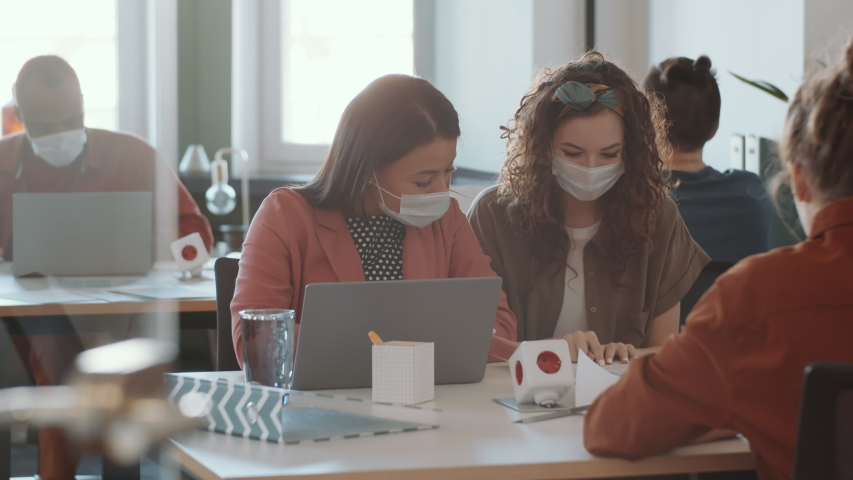Two female colleagues in protective face masks sitting together at desk and discussing project on laptop while working in office during Covid-19 outbreak Royalty-Free Stock Footage #1049532460