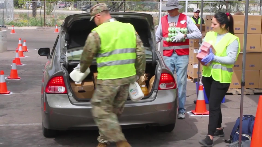 CIRCA 2020 - during the Covid-19 coronavirus epidemic outbreak, members of the armed forces hand out groceries at a food bank in Arizona.