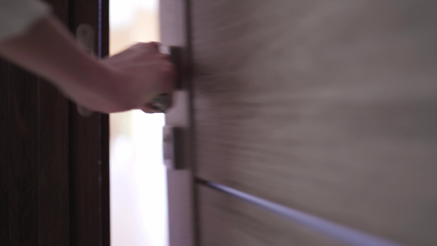 The woman opens the key lock of the door and leaves the room, a close-up static shot. Bright background behind the wooden door | Shutterstock HD Video #1049536666