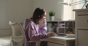 Teenage girl school student wearing wireless headphones conference calling on laptop distance learning at home. Teen schoolgirl chatting by web cam preparing for test or exam with online teacher.