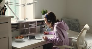 Distance learning concept. Adolescent schoolgirl studying online using laptop making notes in copybook. Teen girl school student wearing headphones watching internet video course sitting at home desk.