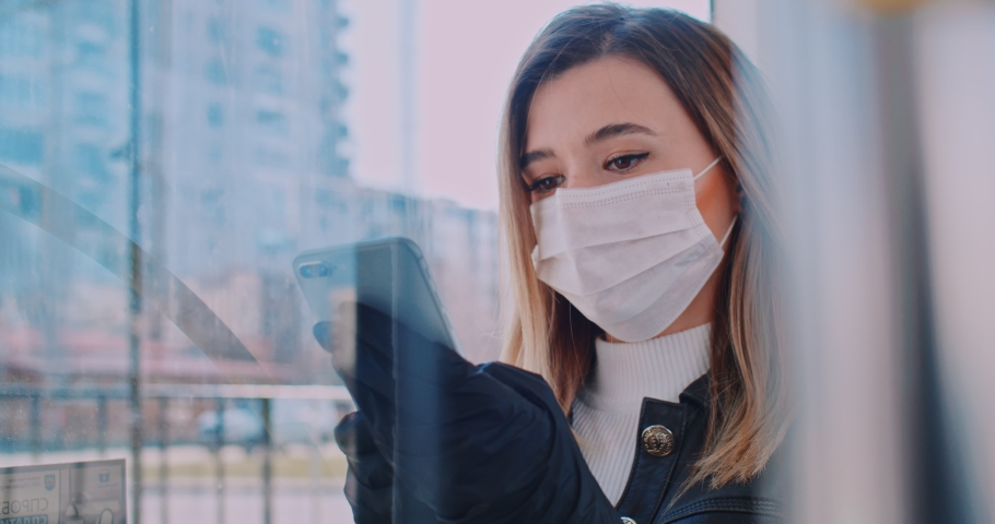 Close up portrait of young smart female volunteer in a medical mask is texting on the phone at bus stop. Quarantine COVID-19 in Europe. Coronavirus transmission in public transport. | Shutterstock HD Video #1049545783