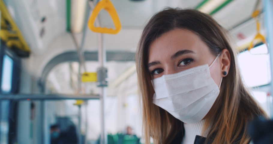 Close up portrait of smart scared female student in medical mask and gloves alone staying at public transport and looking to camera. Commute bus has few passengers. | Shutterstock HD Video #1049545900
