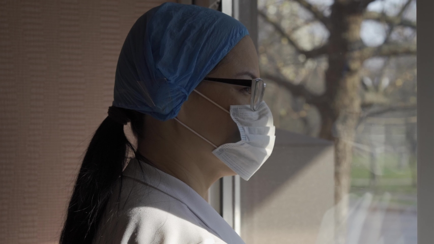 Quarantine concept. Asian woman in a surgical mask, glasses and a cap in isolation. She looks through the glass of the window into the street.