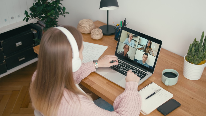 Online Group Video Call Conference of Work Team from Home Office. Woman in Headphones Talks with 4 People at Video Chat using Laptop. Self-isolation at COVID-19 Pandemic. 4K Top View Medium Orbit Shot