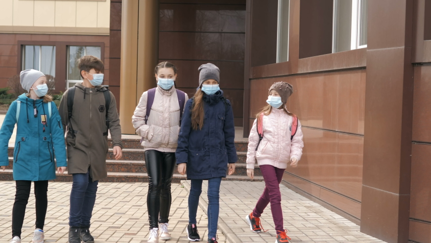 Children students in medical masks leave the school Royalty-Free Stock Footage #1049558128