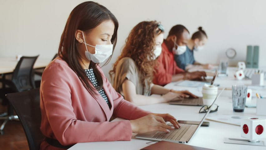 Brunette mixed raced woman in surgical face mask typing on laptop at desk while working in open space office with multiethnic colleagues during coronavirus outbreak Royalty-Free Stock Footage #1049559625