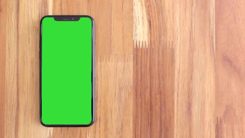 Thailand, Roi-Ed - March 30, 2020 : Smart phone place on table wood with green screen, Close-up the cell phone is on the brown desktop with chroma key, Green screen telephone, slider and top view.
