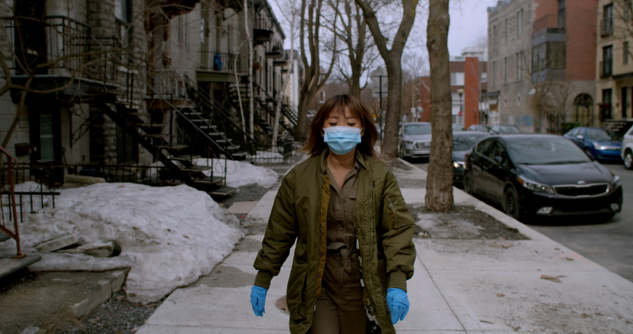 Woman wearing face mask and gloves walks home quickly during the coronavirus pandemic trying to avoid people and any social interaction