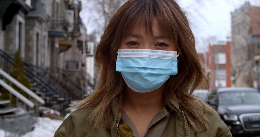 Woman puts on face mask to protect herself from the coronavirus outbreak and pandemic | Shutterstock HD Video #1049560342