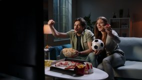 Funny young emotional caucaian sport fan couple watching a game together, eating popcorn and pizza and reacting to their team playing 4k footage