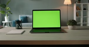 Modern laptop with mock up chroma key green screen on table of living room, desk set up for work at home - technology concept close up zoom 4k video template