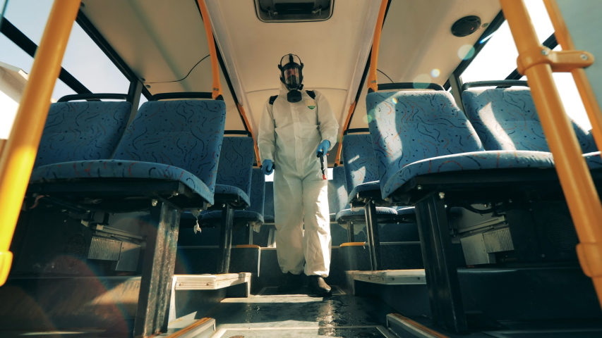 Disinfector is walking along the bus and sanitizing it. Coronavirus prevention, sanitary disinfection process. | Shutterstock HD Video #1049561587