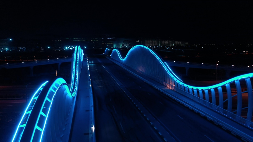 Empty futuristic bridge in Dubai at night. Blue neon light. 4K aerial footage. Modern city concept.  | Shutterstock HD Video #1049566963