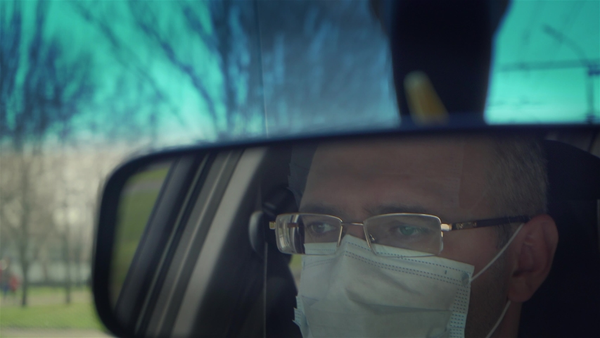 Reflection in back view mirror of man in protective medical mask driving car through city during outbreak of dangerous disease around world. Male in vehicle on town