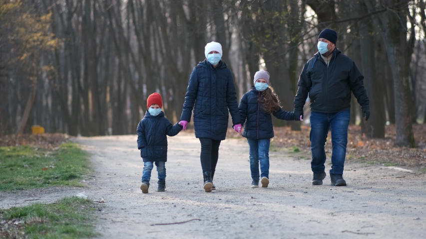 Family: father, mother, son and daughter walk in the Park in medical masks in the spring. The concept of protection FROM covid-19 coronavirus infections. | Shutterstock HD Video #1049575936