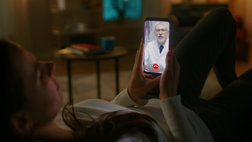 Young Girl Sick at Home Using Smartphone to Talk to Her Doctor via Video Conference Medical App. Woman Has Conversation with Professional Physician, Using Online Video Chat Application. Late at Night